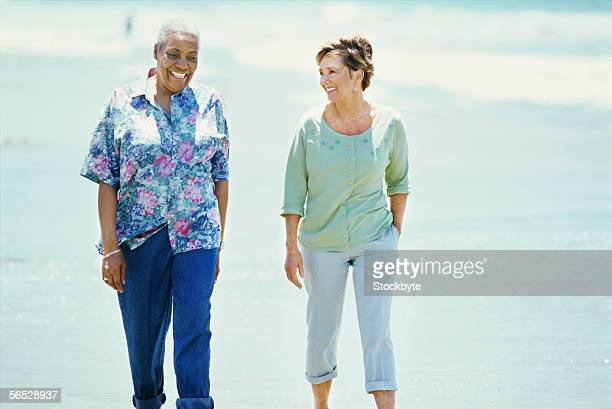 two mature women walking on the beach
