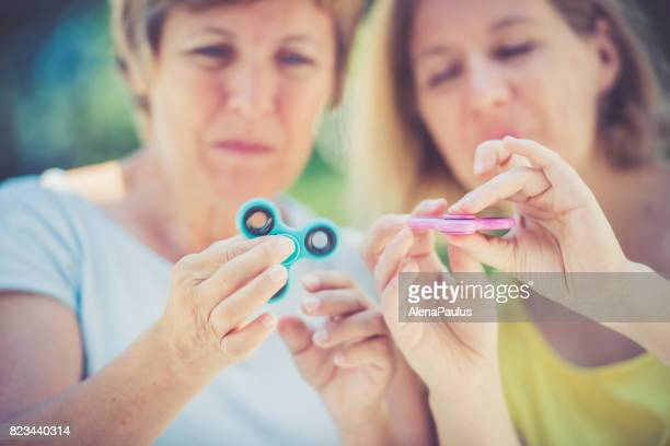 Two mature women with  spinner in hands close up