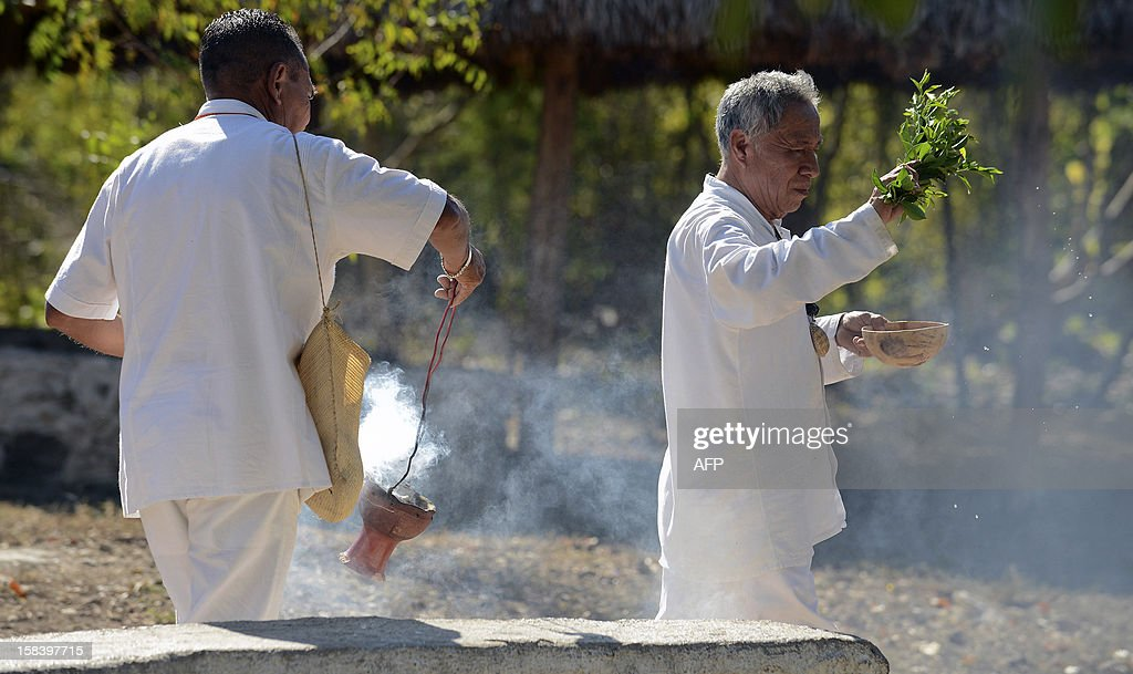 Two Maya priests hold a water blessing ceremony at the Noc Ac cenote -a natural deep deposit of water- in the town of the same name, Yucatan state, Mexico on December 15, 2012 in the framework of the Maya cultural festival, to celebrate the the end of the Maya Long Count Calendar --Baktun 13-- and the beginnig of a new era.