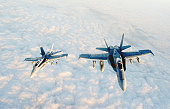 Two McDonnell Douglas F-18 Super Hornets flying in formation