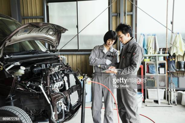 Two mechanic inspecting a damaged car with digital tablet in an auto repair garage