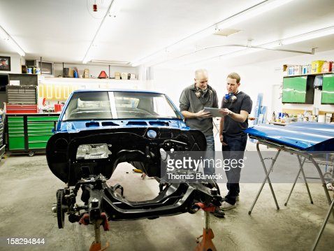 Two mechanics looking at digital tablet in garage : Stock Photo