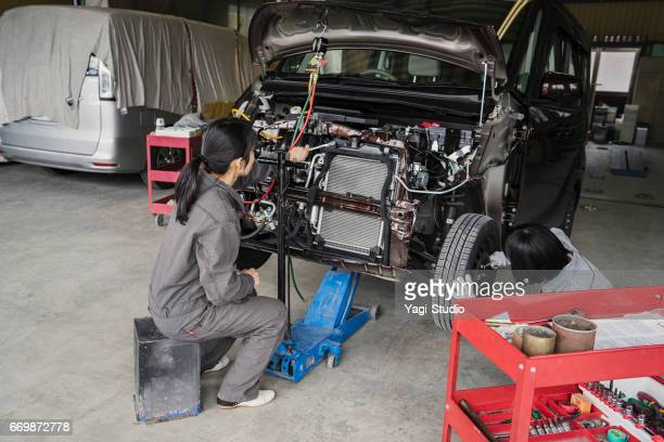 Two mechanics working together in an automotive repair shop