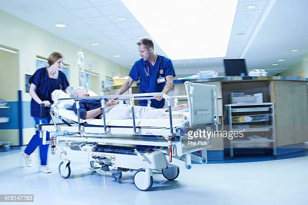 Two medics rushing with gurney in hospital emergency room