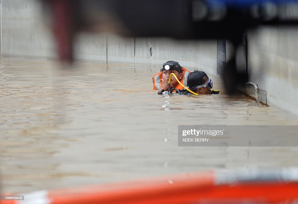 Two members of a search and rescue team enter a gate at the base of the UOB building to help rescue people trapped in a basement after seasonal floods inundated much of downtown Jakarta on January 18, 2013. Floods in Indonesia's capital Jakarta have left at least 11 people dead and two missing, authorities said as murky brown waters submerged parts of the city's business district, causing chaos for a second day. AFP PHOTO / ADEK BERRY
