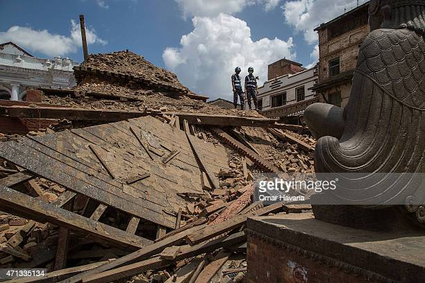 Two members of an emergency rescue team stand on top of the debris of the temples at Basantapur Durbar Square on April 27 2015 in Kathmandu Nepal A...