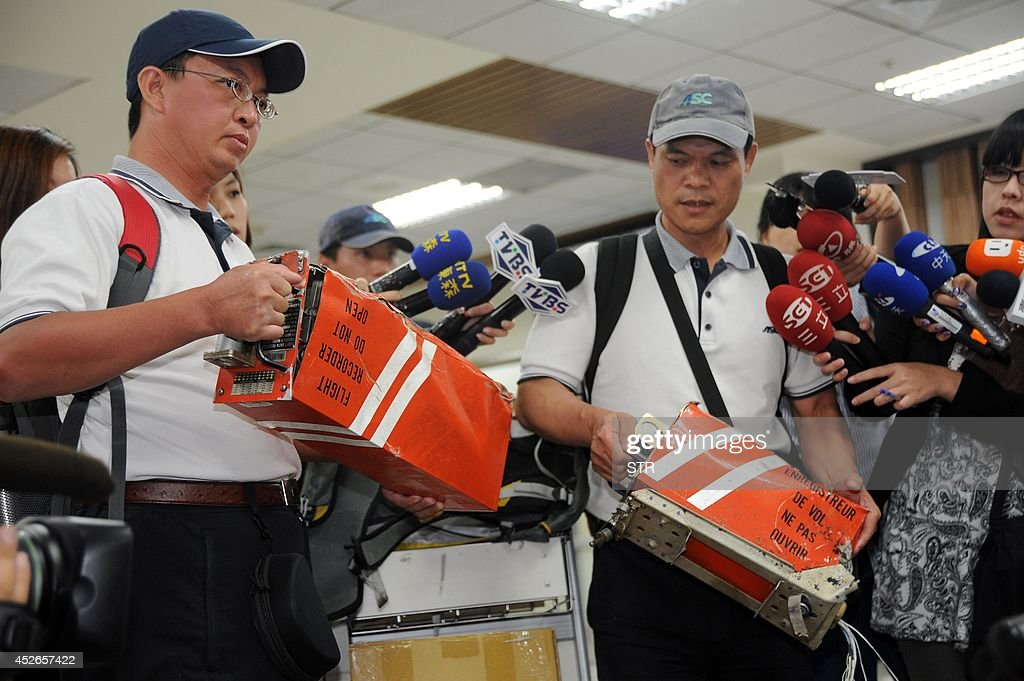 Two members of Aviation Safety Council hold the two black boxes from TransAsia Airways flight GE222 that crashed in the Penghu island chain in Taipei...