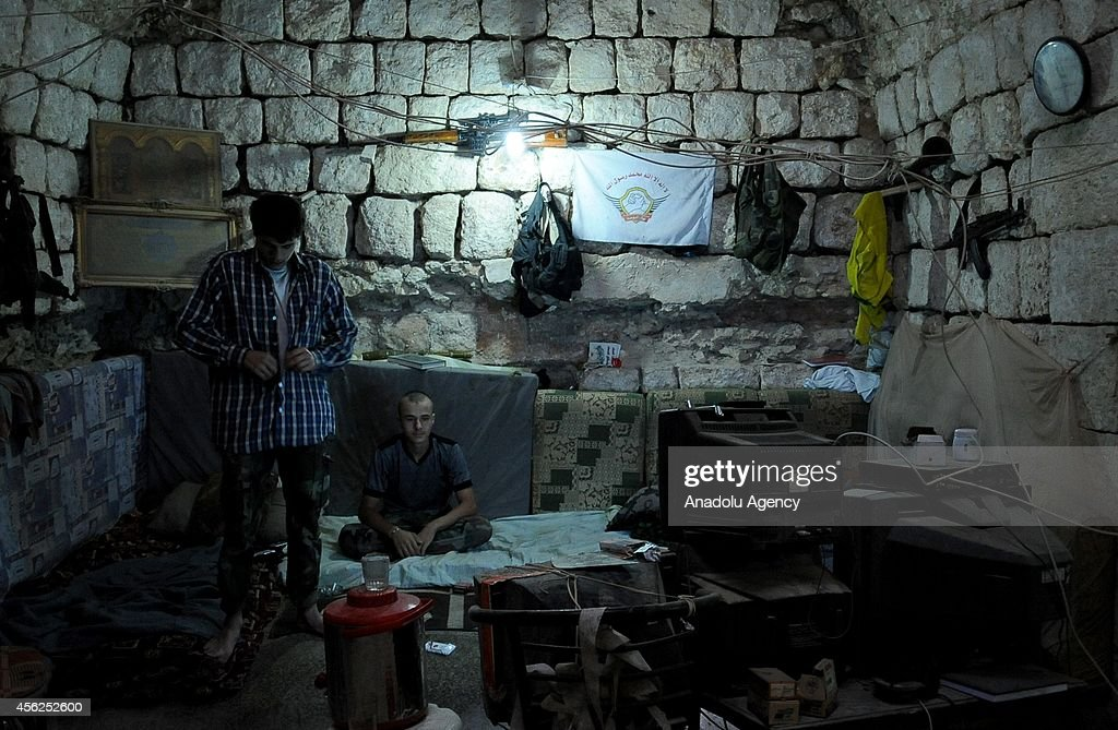 Two members of Islamic Front rest in a shelter, built to hide and to be protected from Syrian Government forces' attacks in Aleppo, Syria on September 28, 2014.