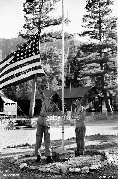 Two members of the Civilian Conservation Corps raise the flag at a camp in the Nevada National Forest Nevada June 1940 | Location Kyle Canyon Nevada...
