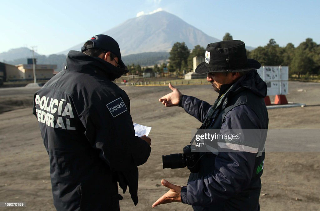 Two members of the Federal Police talk with the Popocatepetl volcano in the background in Paso de Cortez, at the Popocatepetl-Iztaccíhuatl National Park, Puebla state, 55 km southeast of Mexico City, on May 19, 2013. The National Disaster Prevention Centre (CENAPRED) raised the alert level to 'yellow phase three'. AFP PHOTO/J. Guadalupe Perez