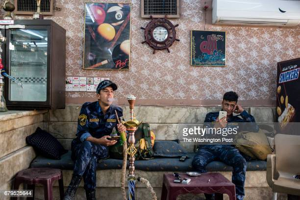 Two members of the Iraqi Federal Police smoke shisha inside Captain a famous billiards club in Mosul Iraq on April 28 2017 Residents of East Mosul...
