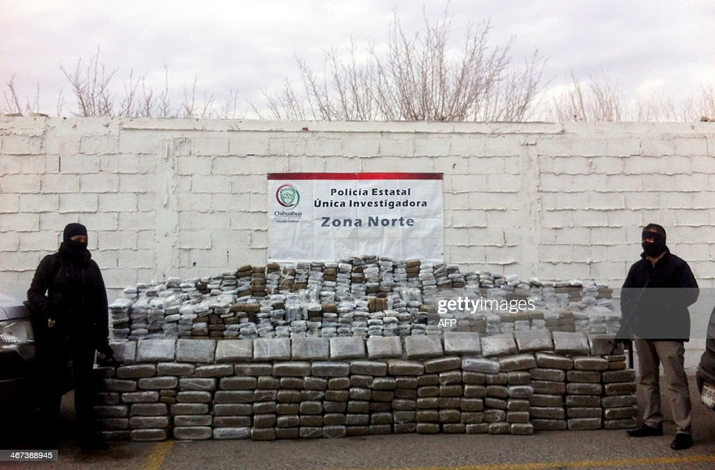 Two members of the Mexican police stand guard next to two tons of seized marijuana in Ciudad Juarez Chihuahua State Mexico on February 06 2014 The...