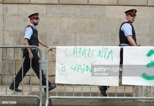 Two members of the Mossos d'Esquadra the Catalonian regional police force walk past a prounion protester's sign outside the Palau de la Generalitat...