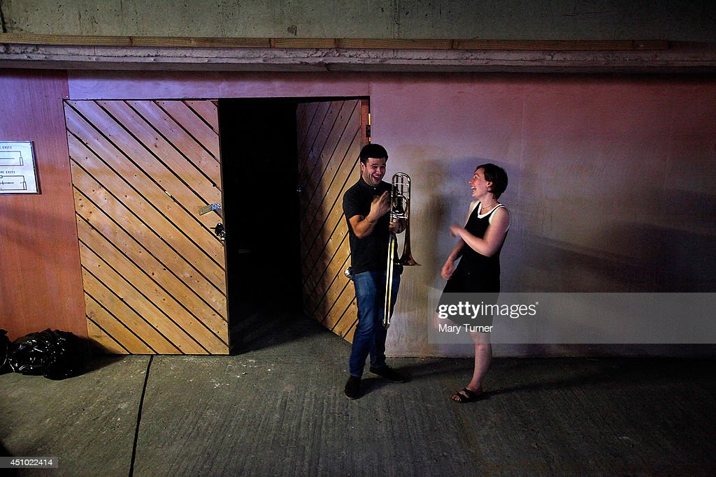 Two members of the MultiStory Orchestra share a joke after a performance of Jean Sibelius' 5th Symphony in the Peckham Rye Car Park on June 21 2014...