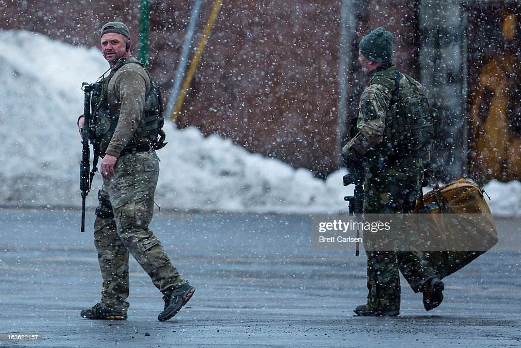 Two members of the New York State Police walk across a vacant parking lot during a standoff with murder suspect Kurt Meyers on March 13, 2013 in Herkimer, New York. Police have identified 64-year-old Kurt Meyers as a possible suspect responsible for a total of four shooting deaths and two injuries across the area earlier in the day.