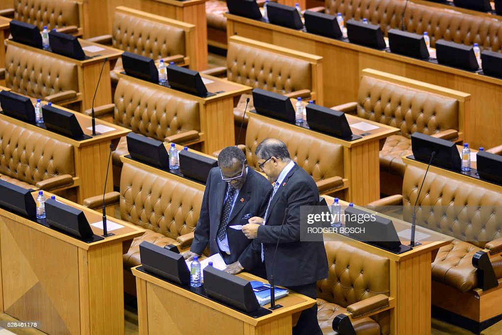 Two members of the smaller opposion party of the Inkatha Freedom Party (IFP), talk at the South African Parliament among empty seats, as most of the opposition parties were boycotted or suspended from the sitting, on May 5, 2016, in Cape Town. The day before, all the members of the opposition party of Economic Freedom Fights (EFF), were manhandled out of the chamber for disrupting a debate on the budget. / AFP / RODGER