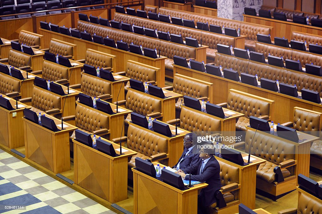 Two members of the smaller opposion party of the Inkatha Freedom Party (IFP), sit at the South African Parliament among empty seats, as most of the opposition parties were boycotted or suspended from the sitting, on May 5, 2016, in Cape Town. The day before, all the members of the opposition party of Economic Freedom Fights (EFF), were manhandled out of the chamber for disrupting a debate on the budget. / AFP / RODGER