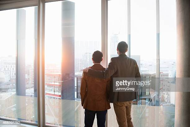 Two men admiring city through window