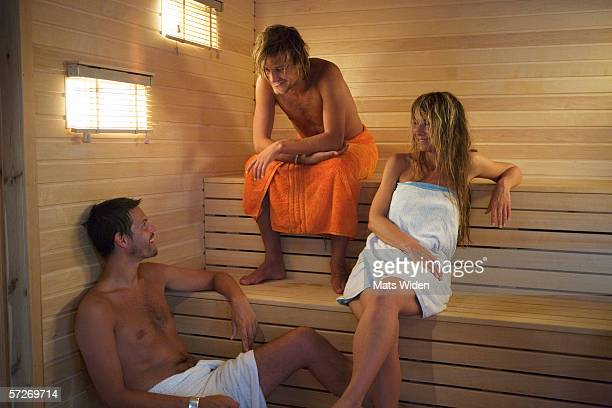Two men and a woman in a sauna.