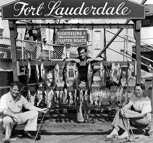Two men and a woman pose on a dock with a group of snook caught on fly in Fort Lauderdale Florida in 1942