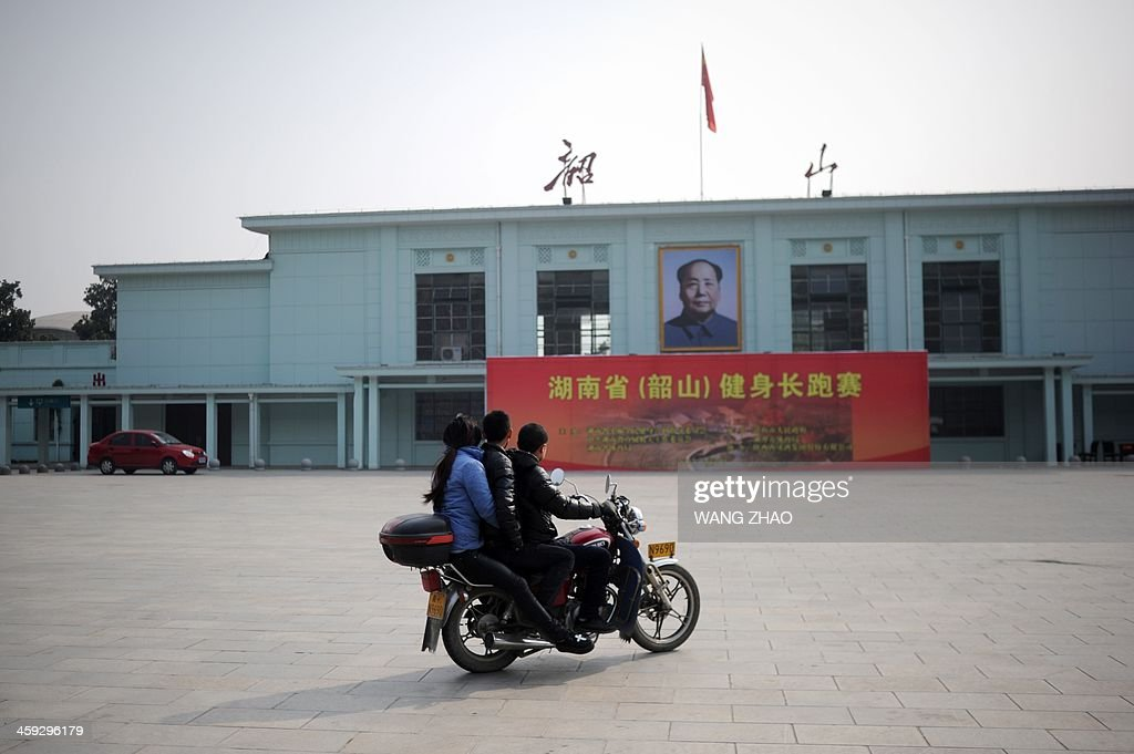 Two men and a woman ride a motorcycle at a railway station displaying a portrait of former Chinese leader Mao Zedong in Shaoshan, in China's central province of Hunan on December 25, 2013. Thousands of admirers of Communist China's founder Mao Zedong flocked to his home town on December 25 to bow before his graven image -- including one statue of solid gold -- before the 120th anniversary of his birth.