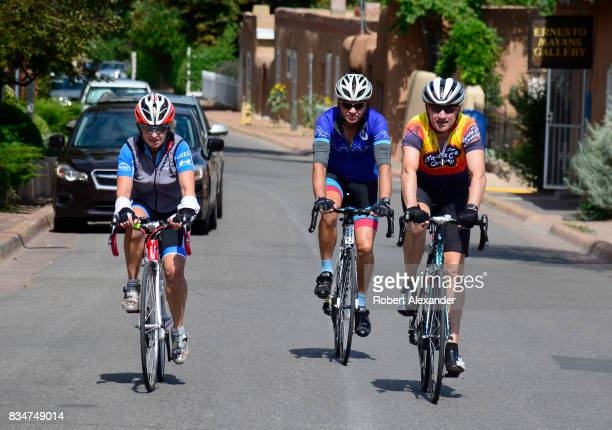 Two men and a woman ride their bicycles along Canyon Road home to dozens of art galleries in Santa Fe New Mexico