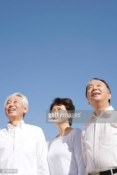 Two men and a woman smiling, looking up