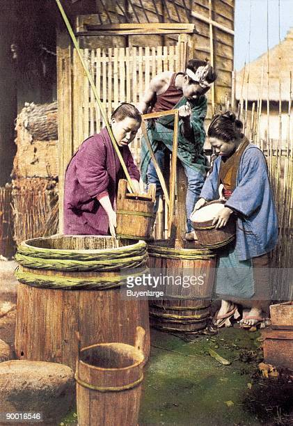 Two men and a women are preparing rice in large barrels used as washing machines