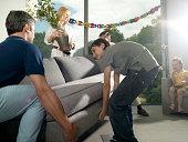 Two men and boy lifting sofa