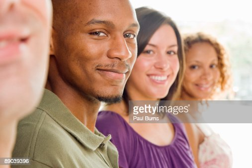 Two Men and Two Women Standing in a Row Smiling : Stock Photo