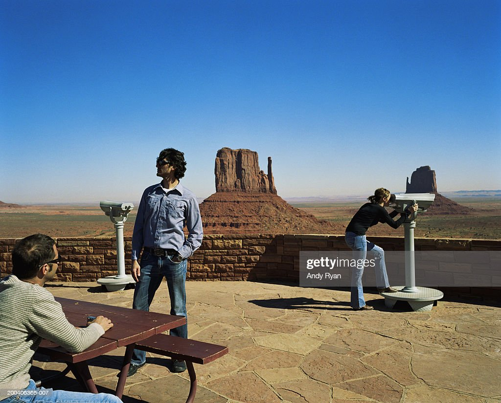 Two men and woman at viewing point in desert landscape : Stock Photo