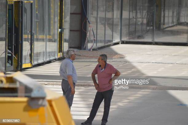 Two men are seen at the construction site of Turkey's biggest retractableroof shopping mall which will be opened in September in Ankara Turkey on...