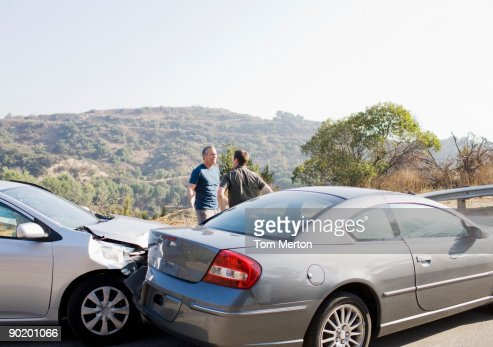Two men arguing about damaged cars
