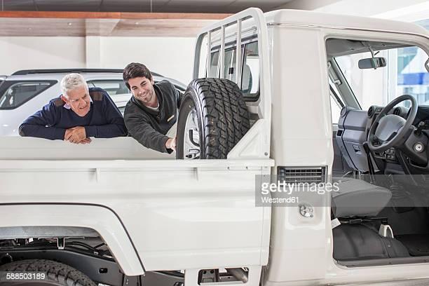 Two men at car dealer examining pick up truck