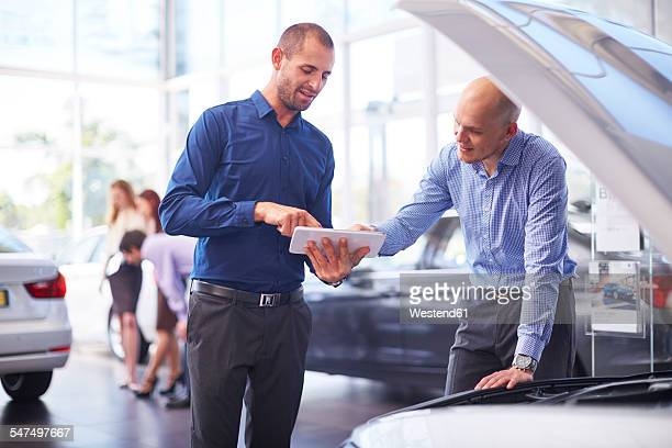 Two men at car dealer with digital tablet