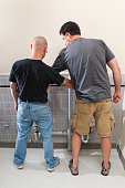 A stock photo of two men, short and tall, standing at urinals in a bathroom as they size each other up.
