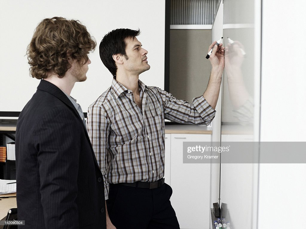 Two men at white board : Stock Photo