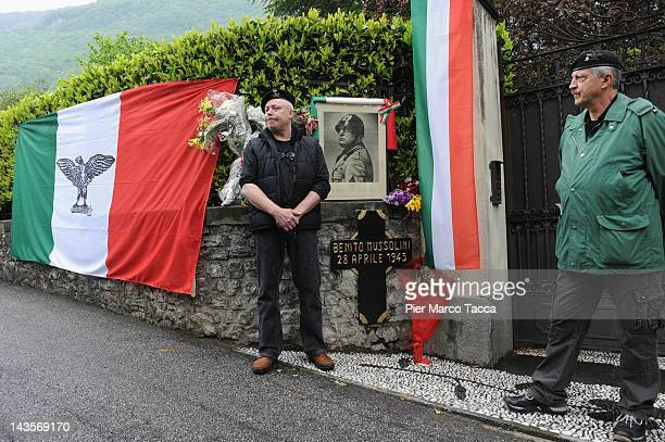 Two men attends a commemoration ceremony for the death of Italian dictator Benito Mussolini and his mistress Claretta Petacci in front of a headstone...