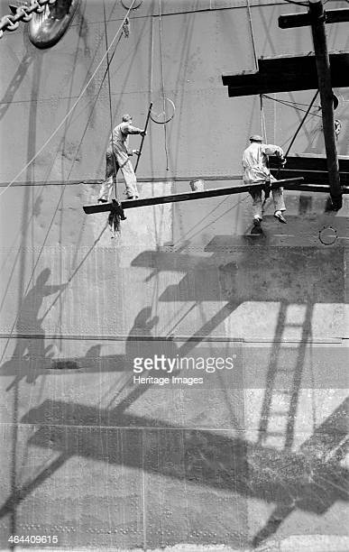 Two men balanced on a plank of wood painting the hull of a large ship in the Royal Albert Dock Canning Town London c1945c1965 A bucket is balanced on...
