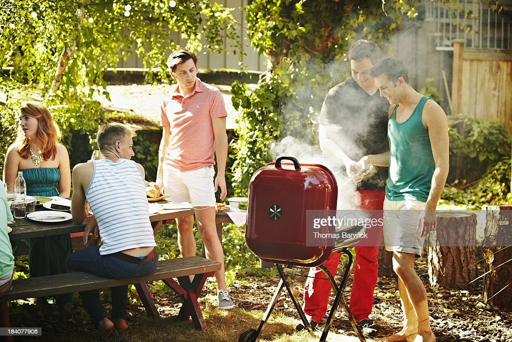 Two men barbecuing together in backyard : Stock Photo