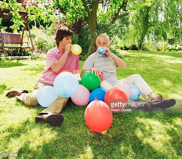 Two men blowing up balloons in garden