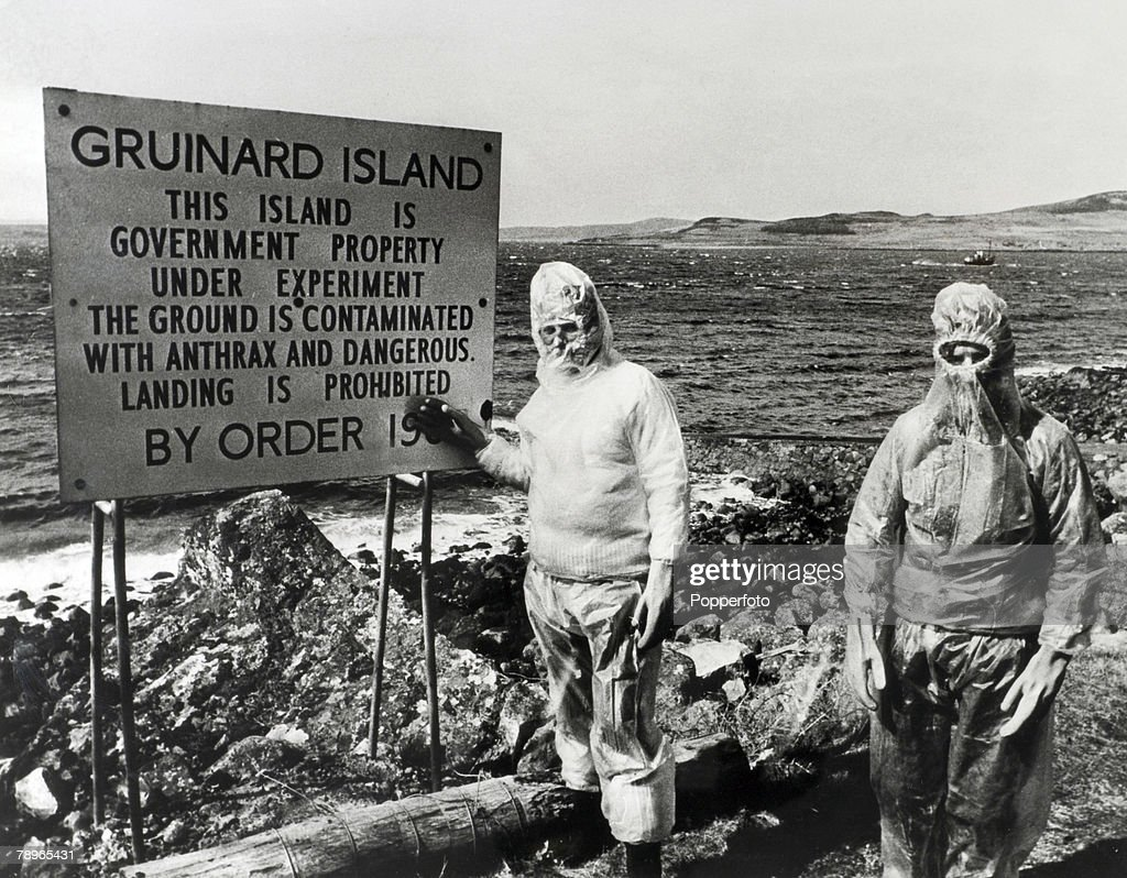 War and Conflict World War Two Scotland Circa 1940's Two men wearing protective clothes stand by a sign on Gruinard Island This small island off the...