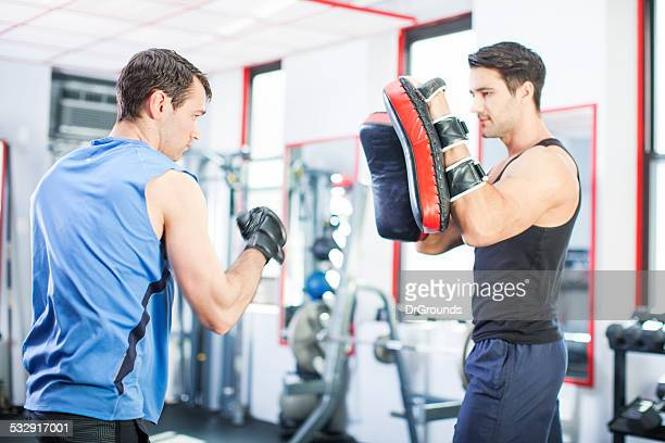 Two men boxing training in gym