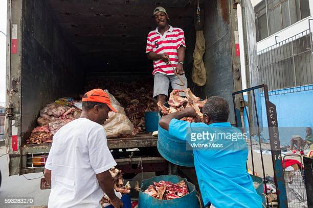 Two men bringing discarded meat and bones that have been collected and is now being loaded onto a truck to be delivered to a soap factory