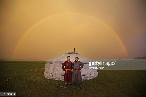 Two men by a ger under a rainbow