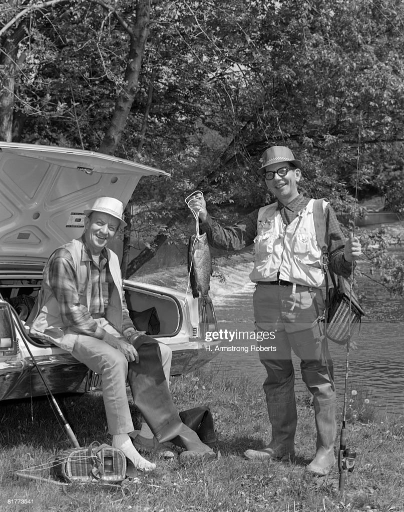 Two men by car dressed in fishing gear, holding catch outside. : Stock Photo