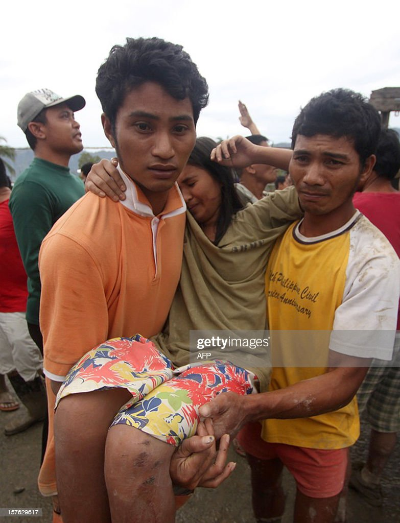Two men carry an injured woman to a Red Cross tent in the aftermath of Typhoon Bopha in New Bataan, Compostela Valley in the southern Philippines on December 5, 2012. The death toll from a typhoon that ravaged the Philippines jumped to 238 on December 5 with hundreds missing, as rescuers battled to reach areas cut off by floods and mudslides, officials said. AFP PHOTO / Karlos Manlupig