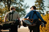 Two men carry golf bags