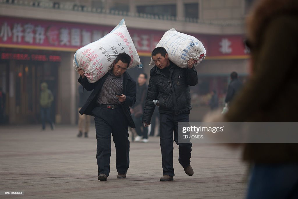 Two men carry their luggage as they arrive at Beijing Railway Station in Beijing on January 27, 2013. The world's largest annual migration began in China with tens of thousands in the capital boarding trains to journey home for next month's Lunar New Year celebrations. AFP PHOTO / Ed Jones
