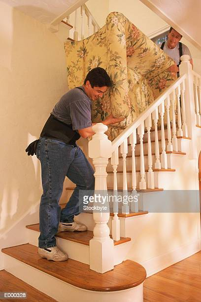Two men carrying couch up stairs